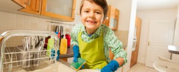 A young boy wearing an apron and rubber gloves helps to wash dishes in the kitchen