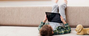 child laying on a couch and using a tablet
