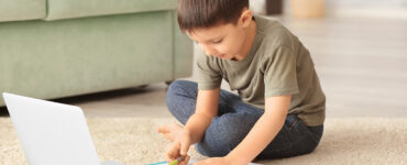 little-boy-does-virtual-school-from-living-room-with-laptop-paper-and-pencil